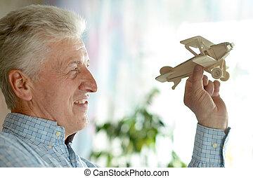 Senior man with wooden plane - Senior man with wooden plane...