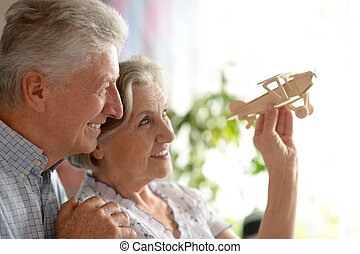 Senior couple with wooden plane at home