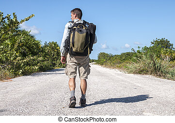 Road hiker - Male hiker with backpack and gear walking alone...