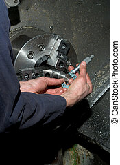 Measuring diameter on lathe - Hands measuring diameter of...