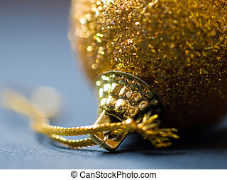 Close-up of a gold christmas ball hanging on Christmas tree...