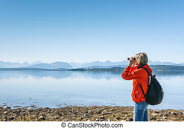 Woman tourist looking through binoculars at distant Atlantic...