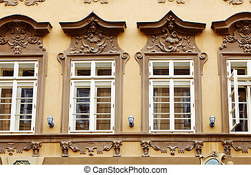 fragment of old facade at a historic building with windows