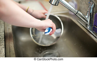Woman washes metal bowl in kitchen sink