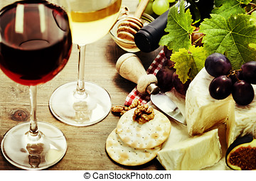 Wine, grape and cheese on wooden background