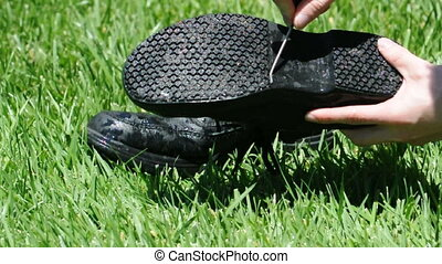 Cleaning black shoes with a hose on grass