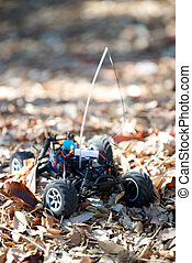 Veritcal of toy RC truck in leaves, no body
