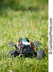 Vertical of toy RC truck in grass, no body