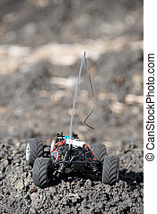 Veritcal of toy RC truck on dirt mound, no body