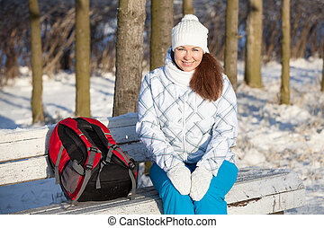 Attractive woman sitting on park bench at winter season