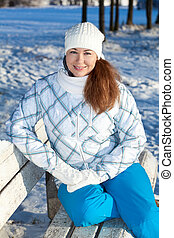 Happy woman sitting on park bench at winter season