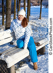 Woman sitting on park bench at winter season