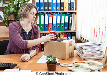 Fired office employee packing personal belongings in box