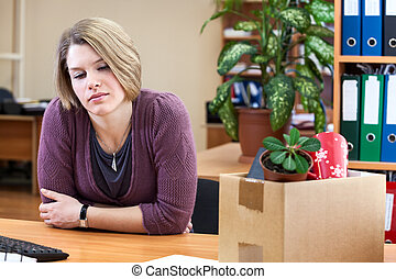 Dismissal - frustrated woman at a desk with a box with...
