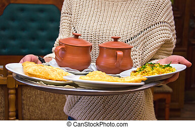 tray of pasties and pots in hands of server