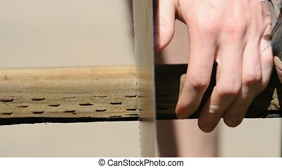 A piece of lumber is cut with a hand saw