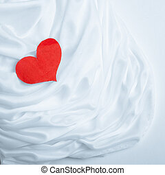 Red heart on white silk fabric