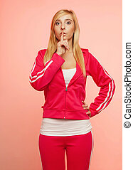 Secret woman. Fitness girl showing hand silence sign