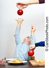 Happy childhood. Boy child kid reaching for apple fruit. At...