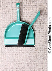 Green sweeping brush and dustpan on floor - housework -...