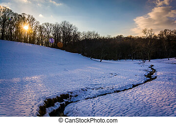 Sunset over a stream in a snow-covered field in rural Baltimore County, Maryland.