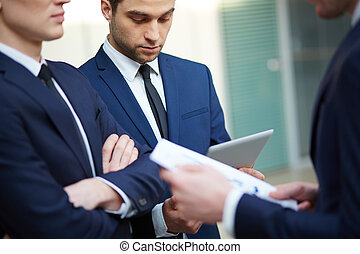 Business discussion - Image of three young businessman using...