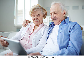 Seniors networking - Senior couple with touchpad sitting at...