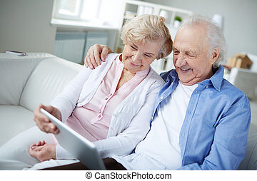 Modern grandparents - Senior couple with touchpad sitting at...