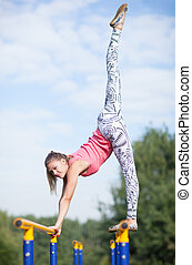 Agile young gymnast balancing on cross bars
