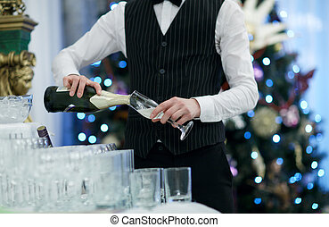 Waiter pouring glasses of champagne at a party or festive...