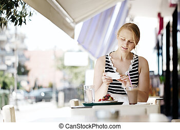 Attractive woman taking picture of a pastry on her mobile -...