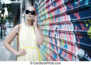 Woman chatting on her mobile in front of graffiti
