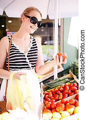 Young woman shopping for fresh tomatoes at an open-air stall...