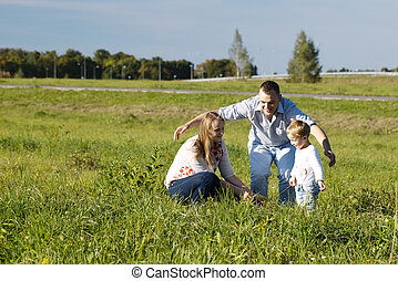 Protective father playing with his wife and son in a grassy...