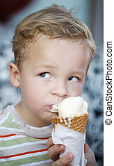 Cute little boy eating an ice cream cone - Cute little blond...