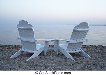 Empty wooden deck chairs on a beach - Empty white painted...