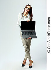 Young laughing businesswoman showing laptop on gray...