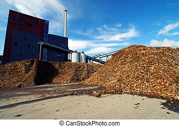 bio power plant with storage of wooden fuel against blue sky...