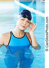 Young woman wearing blue swimming suit and hat in swimming...