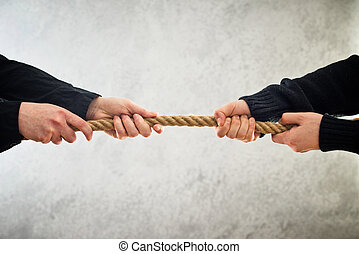 Hands pulling rope to opposite sides - female hands pulling...