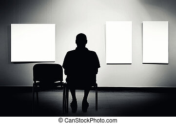 Man sitting in art gallery, looking at art displayed on...