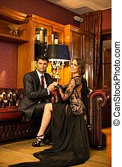 Elegant couple in formal dress in luxury cabinet interior