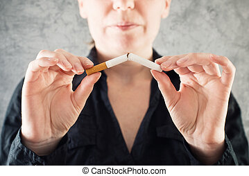 Woman quits smoking and breaking cigarette in half. healthy...