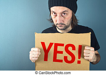 Man holding cardboard paper with word Yes