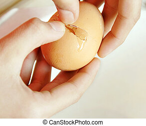 Egg breaking - hands opening broken eggshell of brown raw...