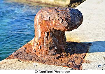 Rusty mooring bollard - Old, rusty mooring bollard on port...