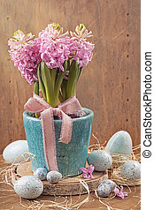 Pink hyacinths in a blue flower pot and easter eggs