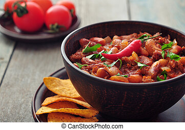 Chili Con Carne in bowl with tortilla chips on wooden...