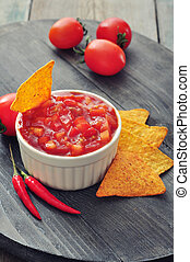 Bowl of salsa with tortilla chips, tomatos and chilli pepper...