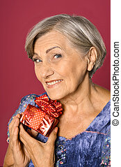 Senior woman with gift box - Portrait of happy senior woman...